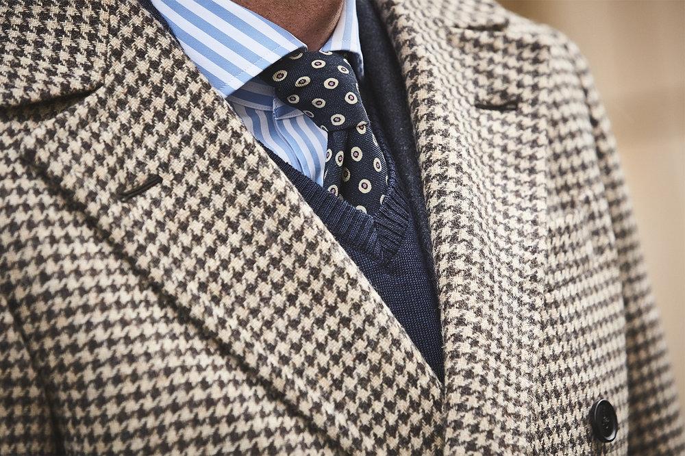 Brązowy płaszcz, granatowy sweter, krawat w kropki i koszula w paski.jpg